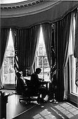 United States President Gerald R. Ford is silhouetted as he works during a quiet moment between appointments in his White House Oval Office in Washington, D.C. on September 4, 1974.  Flanking him are the flags of the United States and the Presidential flag.  Flags of the different Armed Services, one shown at extreme right, are around the windows behind his larger, office desk, partially shown in left background.<br /> Mandatory Credit: David Hume Kennerly / White House via CNP