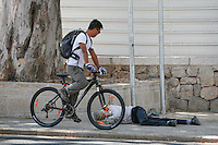 Israeli man Lying in the street at the center of Jerusalem while a bicycle rider passing by. June 30, 2013. Photo By Oren Nahshon