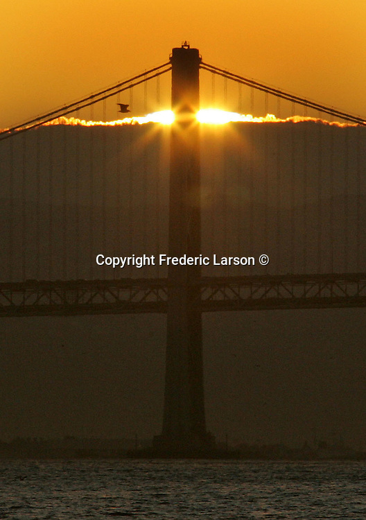 The sun rose  directly over a layer of fog at the south tower of the Golden Gate Bridge in California.