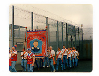 A photograph showing Tommy and friends inside the Maze prison marching on the 12th July. 'The Twelfth' (also known as Orangemen's Day) which celebrates the 'Glorious Revolution' of 1688 (when Protestant king William III ascended the English throne) and the Battle of the Boyne (when William III defeated the catholic claimant James on the east coast of Ireland) is celebrated each year on the 12th of July. (The Maze prison, on the site of a former Royal Airforce station of Long Kesh on the outskirts of Lisburn in Northern Ireland was used during the Troubles (a period of intercommunal violence and strife which lasted for approximately 3 decades from the 1960s to 1998, when the Good Friday Agreement ended outright hostilities) to house paramilitary prisoners. It was closed in 2000 and partly demolished.).