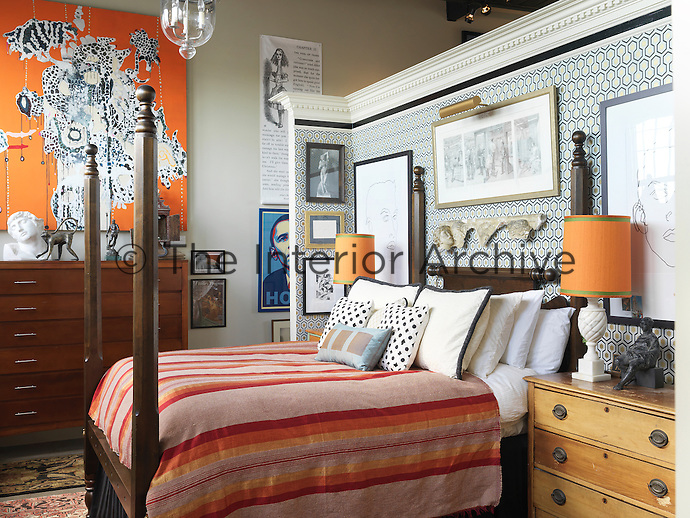 """A partition creates a bedroom and the warm orange tones of a large abstract painting, """"Bettys Revenge"""" by Laurel Sparks, are echoed in the bedding and table lamps"""