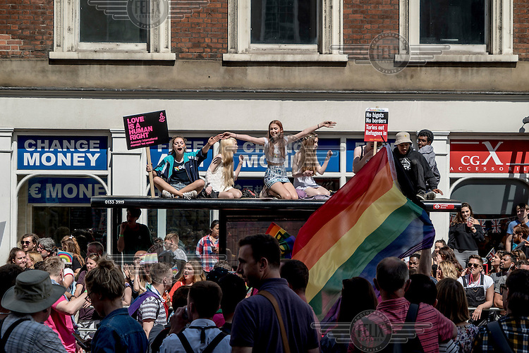 Revellers in Whitehall sit on the roof of a bus stop during Gay Pride.