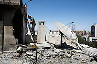 A Syrian soldier climbs down a ladder on the roof of an apartment block that was hit by two unknown projectiles, in Damascus, Syria. The Syrian military claimed the projectiles were fired by rebels in the city's suburbs, but the scale of the destruction suggest possible stray Syrian army shells.
