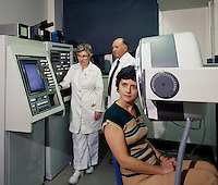 Test being performed on a woman's head by a large machine.