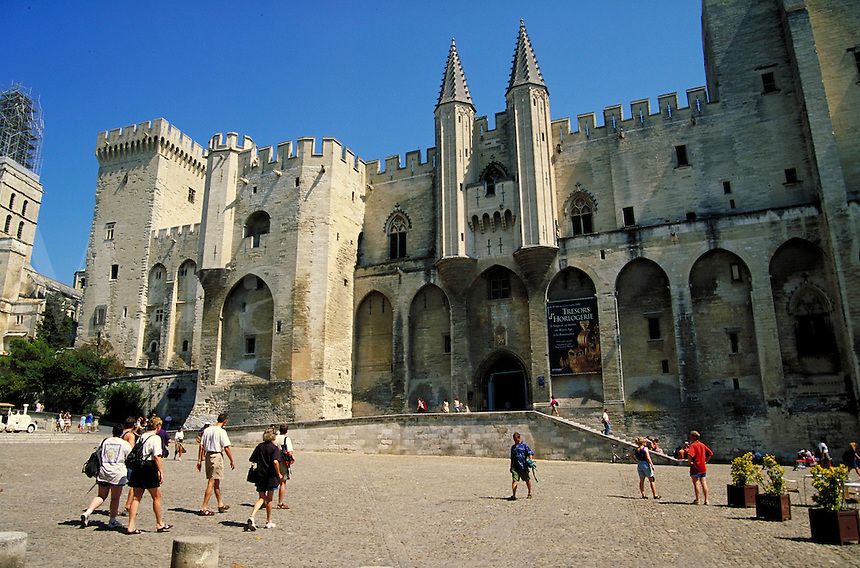 Part of facade of the Palace of the Popes and the broad, sunny plaza it faces. Banner announces Tresors d'Horlogerie (Treasures of Timepieces) exhibition. People and planterboxes. Avignon Provence France.