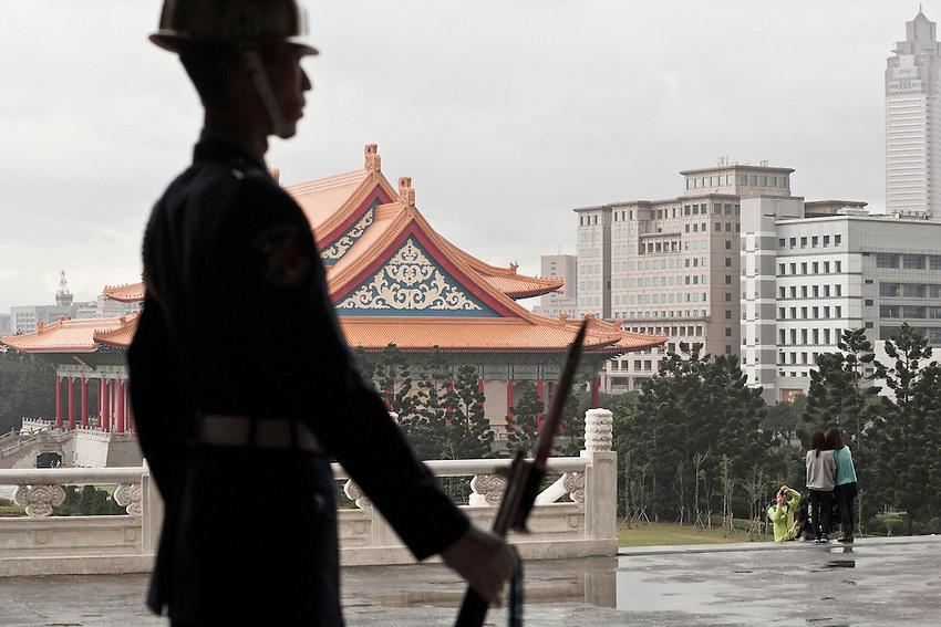 Un soldat à l'entrée du mausolée pendant que des jeunes taiwanais se prennent en photo. Au fond le Taiwan National concert Hall.