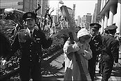 Police remove an old gentleman carrying a huge wooden crucifix from infront of the American embassy where he had been protesting against the war in Iraq.. Tokyo, japan.