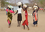 Displaced women carry home grain on their heads in Agok, a town in the contested Abyei region where tens of thousands of people fled in 2011 after an attack by soldiers and militias from the northern Republic of Sudan on most parts of Abyei. Although the 2005 Comprehensive Peace Agreement called for residents of Abyei--which sits on the border between Sudan and South Sudan--to hold a referendum on whether they wanted to align with the north or the newly independent South Sudan, the government in Khartoum and northern-backed Misseriya nomads, excluded from voting as they only live part of the year in Abyei, blocked the vote and attacked the majority Dinka Ngok population. The African Union has proposed a new peace plan, including a referendum to be held in October 2013, but it has been rejected by the Misseriya and Khartoum. The Catholic parish of Abyei, with support from Caritas South Sudan and other international church partners, has maintained its pastoral presence among the displaced and assisted them with food, shelter, and other relief supplies.