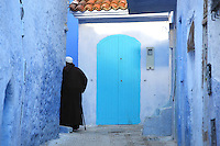 Man wearing a djellaba turning a corner of a narrow street painted blue in the medina or old town of Chefchaouen in the Rif mountains of North West Morocco. Chefchaouen was founded in 1471 by Moulay Ali Ben Moussa Ben Rashid El Alami to house the muslims expelled from Andalusia. It is famous for its blue painted houses, originated by the Jewish community, and is listed by UNESCO under the Intangible Cultural Heritage of Humanity. Picture by Manuel Cohen