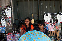Young Muslim couple sell shoes. slippers and other products from their pavement stall in Port Louis.<br /> Iklaas and Malika Myran at their stall.