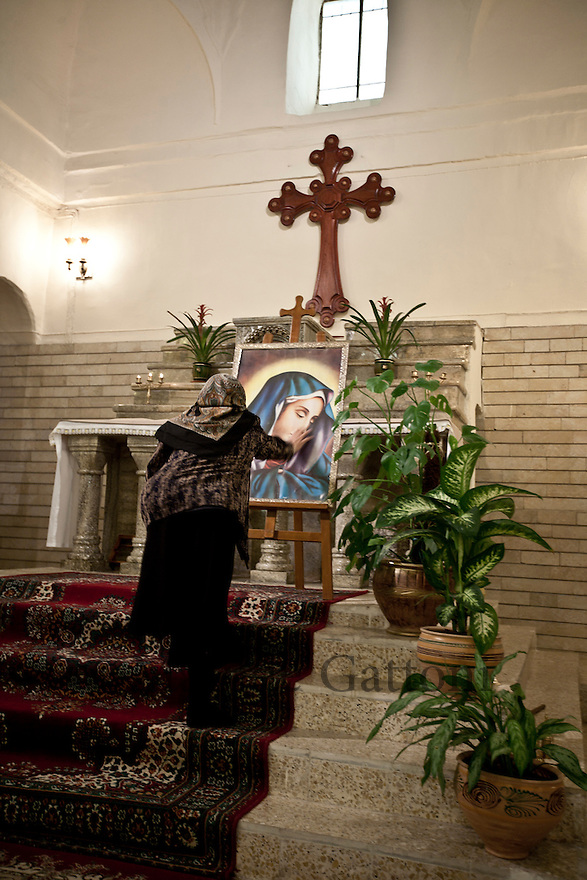 Iraq - Kurdistan - Ankawa -  Christian woman touching the image of the Virgin Mary inside St George Church