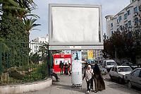 Donne arabe velate passano sotto un grande cartellone pubblicitario vuoto Femmes arabes voilées sous sous un grand panneau d'affichage, Arab women veiled pass under a large blank billboard