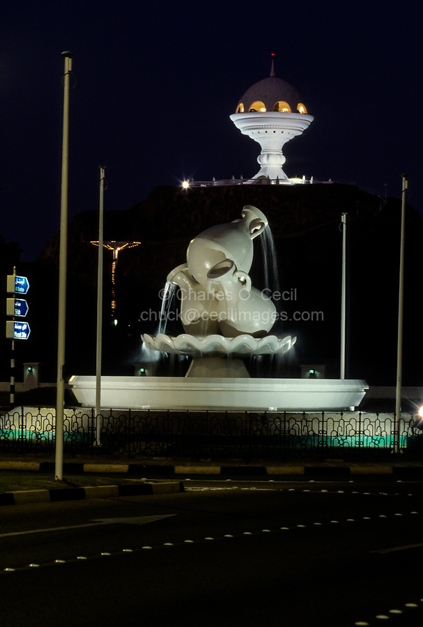 Muscat, Oman.  Monumental Incense Burner and Roundabout with Water Pot Replicas at Night.