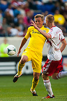 Aaron Schoenfeld (18) of the Columbus Crew is marked by Markus Holgersson (5) of the New York Red Bulls. The New York Red Bulls and the Columbus Crew played to a 2-2 tie during a Major League Soccer (MLS) match at Red Bull Arena in Harrison, NJ, on May 26, 2013.