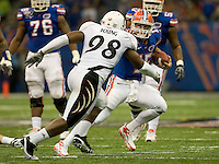 01 January 2010:  Tim Tebow of Florida runs the ball away from Curtis Young of Cincinnati during Sugar Bowl at the SuperDome in New Orleans, Louisiana.  Florida defeated Cincinnati, 51-24.
