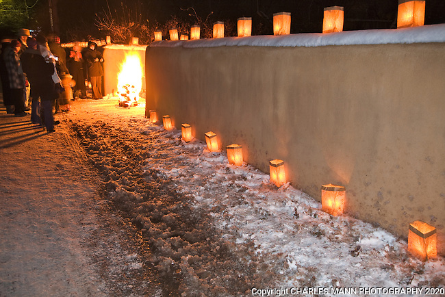 Walls and walks are lined with paper bag faralitos and people warm themselves by small campfires called luminarias during the annual Christmas Eve celebration  on Canyon Road in Santa Fe, New Mexico