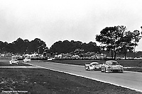 """Sebring historian and press officer Ken Breslauer has stated the 1983 race was the biggest upset in Sebring history, when Wayne Baker, Kees Nierop and Jim Mullen drove their GTO-class Porsche 934 to victory after most of the prototype class fell victim to the track's brutal pounding. In this picture the 934 runs in front of the Nimrod NRA/C2 Aston Martin prototype while another Porsche """"runs wide"""" exiting the Green Park Chicane."""