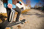 A skateboarder carrying a water bottle enjoys an autumn day at Salt Lake City's Library Square.