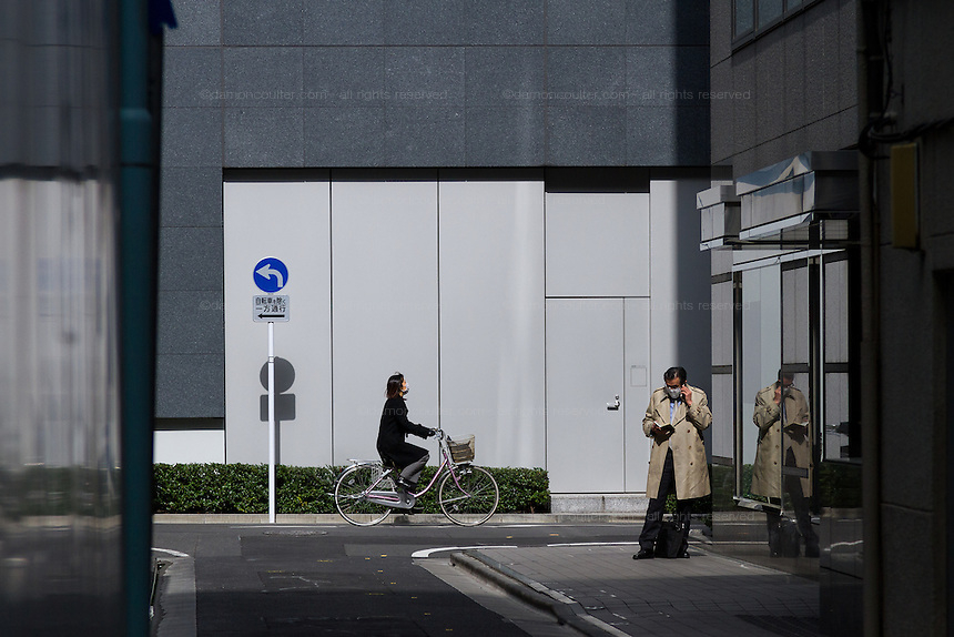 A businessman talks on a mobile phone in a back street near Ginza, Tokyo, Japan Friday March 3rd 2017