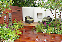 Fireplace pit outdoors on beautiful patio deck with gorgeous landscaping, garden furniture chairs, flames at night for heat and illumination lighting, room outdoors