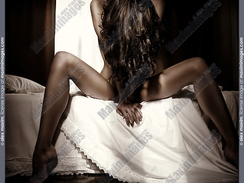 Artistic dramatic portrait of a nude young woman sitting on a bed with long brown hair covering her body