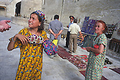 Sellers of carpets and tourist souvenirs sit in the shade outside the Kalan Mosque and Medressa, once an important Islamic studies teaching school in the Old Silk Road city of Bukhara, Uzbekistan
