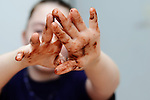 Girl with messy hands with chocolate