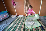 A Syrian girl folds up her bedding inside her family's shelter in the Zaatari refugee camp near Mafraq, Jordan. Established in 2012 as Syrian refugees poured across the border, the Zaatari camp held more than 80,000 refugees by 2015, and was rapidly evolving into a permanent settlement. ACT Alliance member agencies provide a variety of services to refugees living in the camp.<br /> <br /> Parental consent obtained.