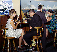 Couples enjoying a drink and a smoke at the bar.