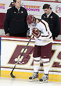 Brendan Silk (BC - 9) works on his stick. He has the initials of his immediate family members written on the tape with ES for his mother Elizabeth visible on one side and JS and LS for sisters Julie and Laura visible on another. - The Boston College Eagles defeated the University of Vermont Catamounts 4-1 on Friday, February 1, 2013, at Kelley Rink in Conte Forum in Chestnut Hill, Massachusetts.