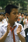 A student claps while singing a patriotic song in the Dong Da primary school exercise yard before attending classes in Hanoi, North Vietnam.  (Jim Bryant Photo)....
