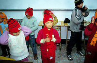 CHINA. Beijing. A young orphan puts on news winter clothes in an orphanage outside of Beijing being visited by a local Christian group. 2007. The orphanage is a mix of orphans and children left for long periods of time by migrant workers who cannot take their children with them. There are currently millions of orphans in China living in orphanages spread throughout the country. As a result of China's one-child policy, many children are abandoned or given up if they suffer from any physical or mental handicap as the parents strive to have a child born 'normal' and well. This has led to may children being abandoned to live in state and privately-owned orphanages.