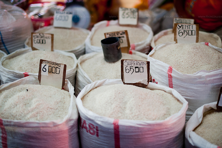 A vendor in Bitung's Aertembaga Market  several different kinds of rice, for sale by the cup or by weight.