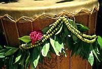 Green leafy maile lei with green mokihana lei from Kaua'i on a Hawaiian drum or pahu.