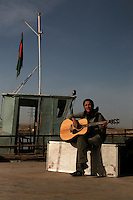 """Maral  with the Kabul based band """"White City"""" playing guitar on the tajik/afghan border boat."""