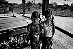 "Mekong Dam Victims - Cambodia. Two girls carrying baskets with empty bottles on their way to the river to collect water. The people still use the water from the river for domestic use, despite the bad water-quality after the construction of dams up-river. At least 55.000 people living near the Sesan river in Cambodia's Ratanakiri and Stung Treng provinces continue to suffer due to lost rice production, lost fishing income, drowned livestock and damaged vegetable gardens, and so also great economical losses, because of the unpredictable floodings from the Yali Falls Dam on the other side of the border in Vietnam. To this day, flash floodings have caused the deaths of at least 39 villagers from various ethnic minority groups living along the river. Despite this, four other major hydropower projects are now in operation or under construction on the Sesan River in Vietnam. Known as ""The Mother of Waters"", more than 60 million people depend on the Mekong river and its tributaries for food, fresh water, transport and other aspects of daily life. The construction of big dams is now threatening the life of these people aswell as the vital and unique ecosystem of the river."