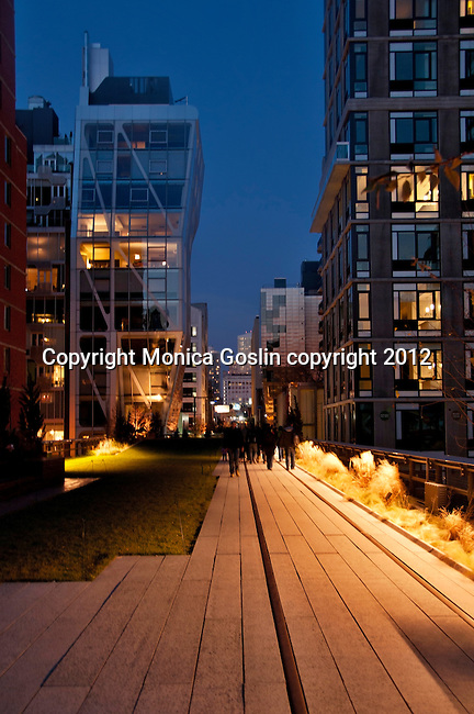 People walking on the Highline (public park on an old elevated train line) at night in New York City