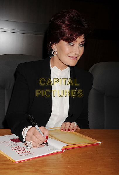 Sharon Osbourne<br /> signs copies of her new book &quot;Mama Hook Knows Best&quot; at Barnes &amp; Noble bookstore at The Grove in Los Angeles, California,<br /> USA, September 18th, 2013.<br /> half length signing pen suit white shirt black jacket sitting <br /> CAP/ROT/TM<br /> &copy;Tony Michaels/Roth Stock/Capital Pictures