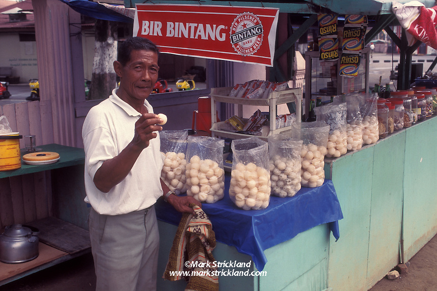 A street vendor shows off his stock of sea turtle eggs.  Sea turtles are endangered worldwide, are officially protected in many countries.  In spite of this, their eggs are still collected and eaten in many parts of the world, putting further stress on dwindling populations. Sumatra, Indonesia, Indian Ocean