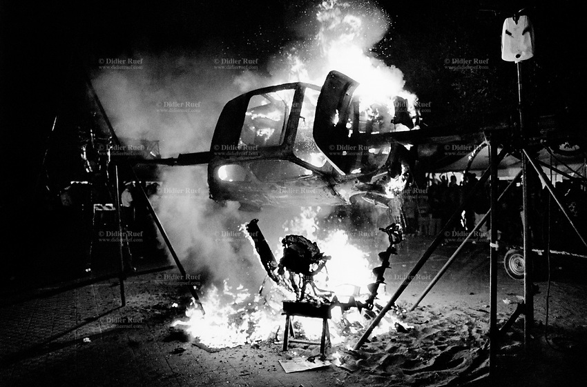 """Italy. Province of Sicily. Menfi. Mutoid Waste Company.  A Fiat 500 is burned on a giant barbecue at """"Inycon"""" festival. Using all types of industrial scrap for their raw materials the Mutoid Waste Company are a mobile and adaptable group of performance artists. Having the necessary equipment to allow them complete freedom, they have created an entirely new form of scultural-musical performance crossing the boundaries of circus, theatre and art. © 1999 Didier Ruef"""