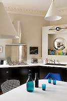 The cupboards in the kitchen are painted black in stylish contrast to the white Corian work surfaces