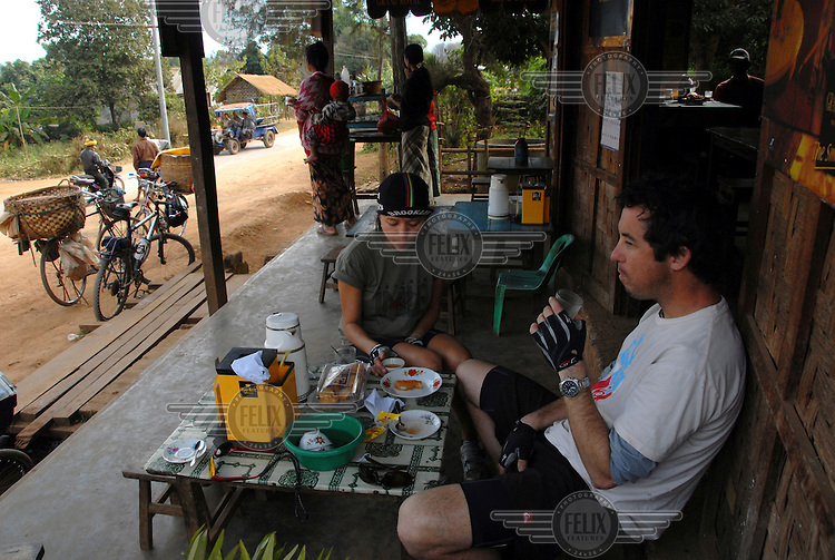 Tea-break in a typical roadside Burmese tea-shop between Kalaw and Ywar Ngan. In December 2007, writer Porter Fox and his friend A'yen embarked on an ambitious cycling trip across Burma.