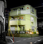 Cheery corner house hemmed in by its neighbors and narrow, busy streets, Seijo, Tokyo, Japan.