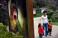 Visitors walk by a picture of a macaque monkey at Monkey Island near Lingshui, Hainan, China.