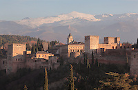 The Alhambra Palace, Granada, Andalusia, Southern Spain, with the Comares Tower (left), built in the 14th century under Muhammad V, the tallest tower in the Alhambra and housing the Hall of the Ambassadors, Nasrid Palaces and the Palace of Charles V in the background, built by Pedro Machuca in the 16th century. The Alhambra was begun in the 11th century as a castle, and in the 13th and 14th centuries served as the royal palace of the Nasrid sultans. The huge complex contains the Alcazaba, Nasrid palaces, gardens and Generalife. Behind are the snow-capped peaks of the Sierra Nevada. Granada was listed as a UNESCO World Heritage Site in 1984. Picture by Manuel Cohen