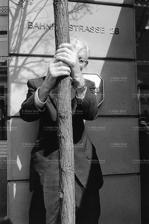 """Switzerland. Zürich. An old man dressed with a black suit, a watch on the left wrist and glasses, holds with both hands the trunck of a tree. He follows on the Bahnhofstrasse ( main banking and shopping street) the parade for the """"Sechseläuten"""" , which celebrates the end of the winter. © 1991 Didier Ruef"""