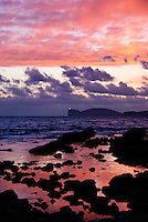 Sun sets pink and purple over Capo Caccia point in Sardinia, Itlay.