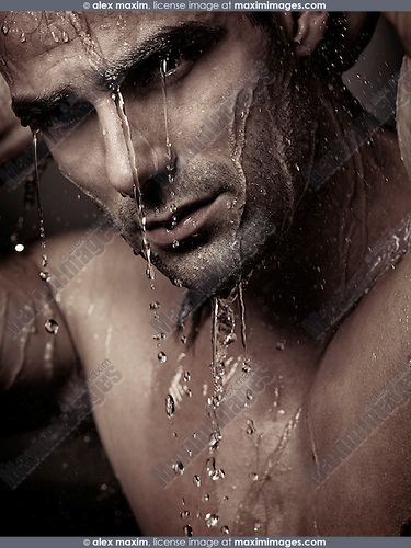 Dramatic portrait of a young man wet face under a shower with water pouring on it