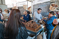 """Customers shop at Grandaisy Bakery at the New Amsterdam Market on South Street in New York during the market's opening day for the season, Sunday, April 29, 2012. The market, located in the former Fulton Fish Market, features vendors who source their artisanal food directly from local farmers and stands of the farmers'  themselves . For opening day they promoted their """"Bread Pavilion"""" which had booths from 16 local artisanal bakeries. (© Richard B. Levine)"""