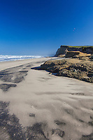 A contoured sandy beach leads to bluffs and a clear blue sky while waves roll gently to shore.